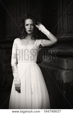 Black-and-white portrait of a beautiful fashion model in luxurious white dress on a city street. Charming bride woman walking down the street. Beauty, fashion.