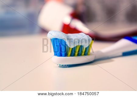 Toothbrush And Toothpaste On Blurred Background