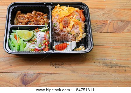fried rice with shrimp paste include mango egg pork onion vegetable in box black / Thai style food on a wood table background