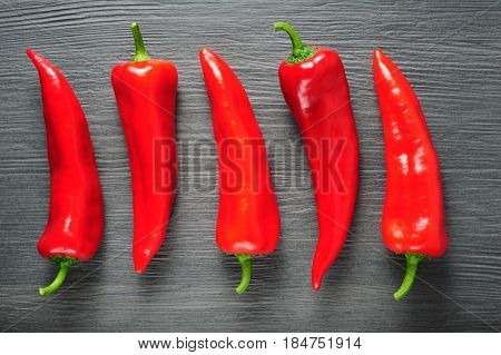 Five ripe sweet red Kapia peppers on dark shale stone background