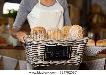 Mid-section of female staff holding wicker basket of various breads at counter in bakery shop