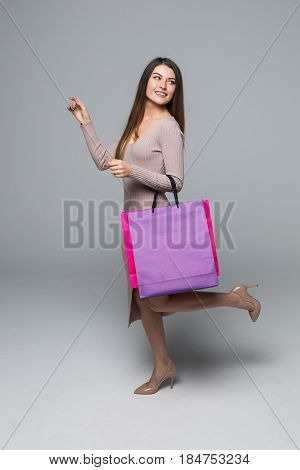 Young Woman Walking With Shopping Bag And Pointed Hand Isolated Over Grey Background