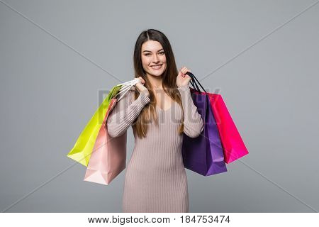 Smiling Young Girl Holding Shopping Bags Isolated On A Grey Background.