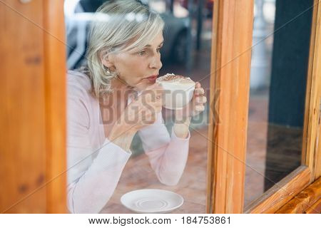 Thoughtful senior woman drinking coffee while sitting by table at cafe shop