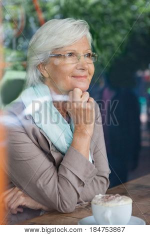 Senior woman looking away while sitting at table in cafe shop