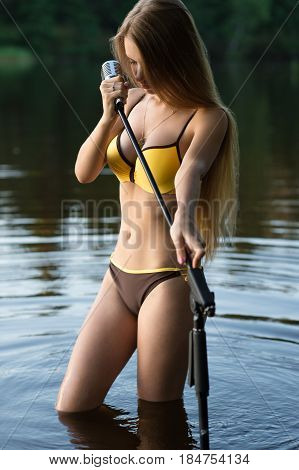 young singer girl with retro microphone standing in water