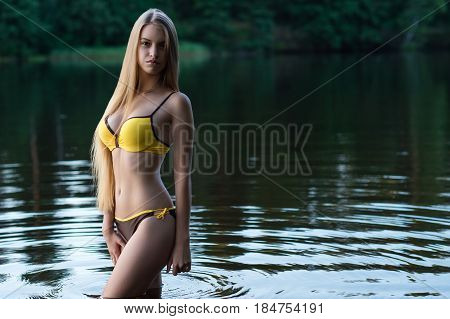 beautiful slender girl teenager in swimsuit standing in water