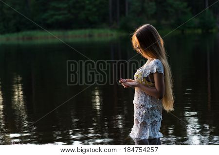 charming young girl in white dress standing in water on sunset
