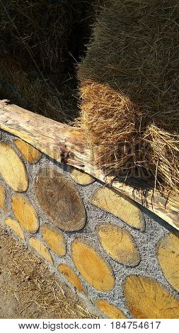 A fragment of a wall of wooden beams and cement and a haystack