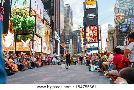 NEW YORK CITY -JUNE 21: People looking street show in Times Square, iconic symbol of New York City and the United States of America, March 21, 2016 in Manhattan, New York City, USA.