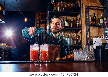 Bartender hipster with a beard makes an alcoholic cocktail behind the counter in the bar.