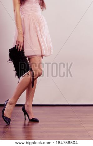 Celebration evening fashion concept - woman in bright dress holding handbag clutch part of body female legs in high heels on party floor