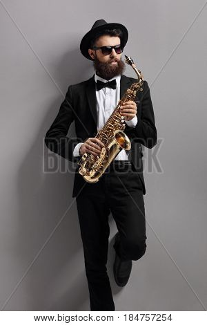 Saxophone player leaning against a gray wall
