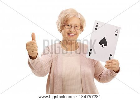 Joyful mature woman showing an ace of spades card and making a thumb up gesture isolated on white background