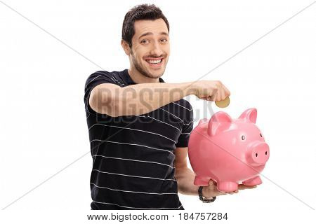 Happy young man putting a coin into a piggybank isolated on white background