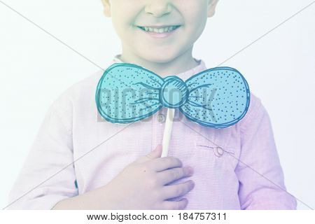 Little boy playing with papercraft bowtie and smiling