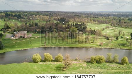 Aerial drone view of the south English countryside on a bright spring day with the foreground dominated by a river grand house and golf course.