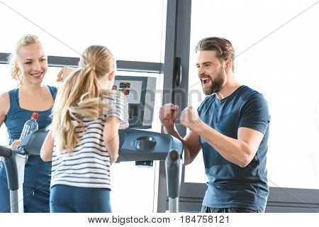 Parents supporting daughter workout on treadmill in gym