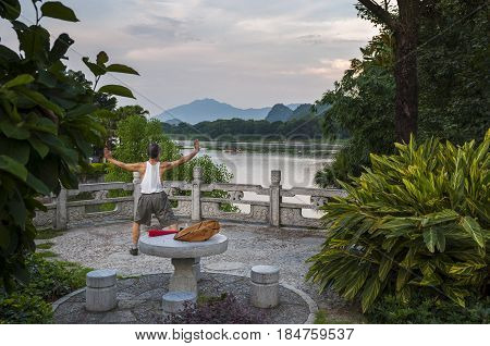 Guilin China - July 31 2012: Man practicing Tai chi in the banks of the Li River in Guilin China.