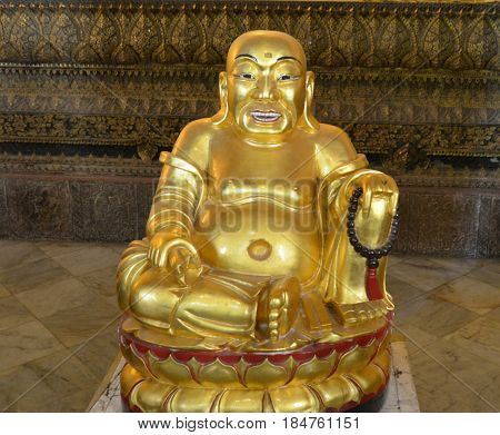 The Golden Buddha sits in the center of the temple convoking pilgrims how to know the mystical knowledge of the philosophy of Buddhism