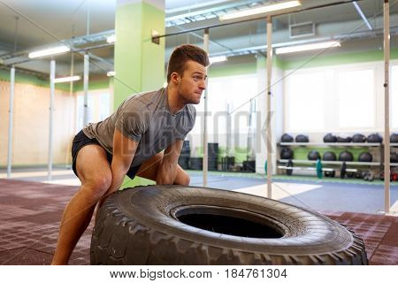 strongman, bodybuilding, sport, fitness and people concept - young man doing tire flip at training in gym