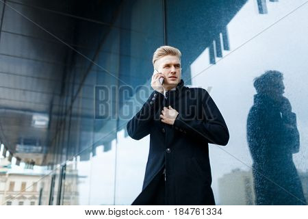 Portrait of concentrated white collar worker having difficult phone conversation while standing against glass outer wall of office building, low angle view