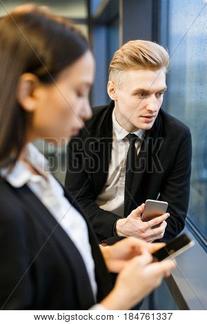Portrait of handsome young white collar worker with smartphone in hand looking out window, his female colleague standing next to him and dialing number of her business partner