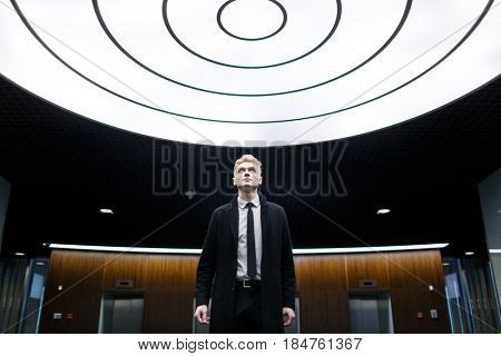 Blond-haired white collar worker posing for photography while standing in office lobby with creative design and looking upwards, portrait shot