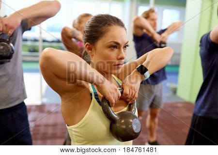 sport, fitness, weightlifting and training concept - group of people with kettlebells and heart-rate trackers exercising in gym poster