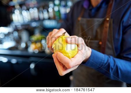 people and profession concept - bartender with peeler removing peel from lemon at bar