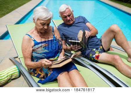 Senior couple reading books on lounge chair at poolside