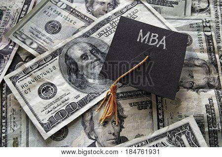 Minil MBA graduation cap on assorted cash -- Masters of Business Administration concept