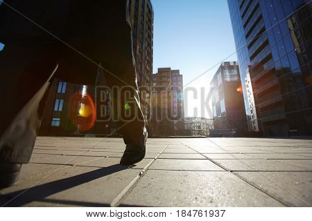 Close-up of male legs walking along city street with modern glass skyscrapers, lens flare