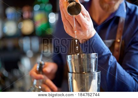 drinks, people and luxury concept - bartender pouring alcohol from jigger into shaker and preparing cocktail at bar