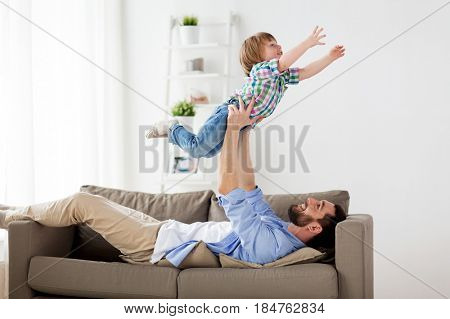 family, fatherhood, people and parenthood concept - happy smiling young father with little son at home