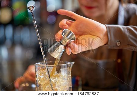 alcohol drinks, people and luxury concept - bartender with jigger pouring syrup into glass jug and preparing cocktail at bar counter