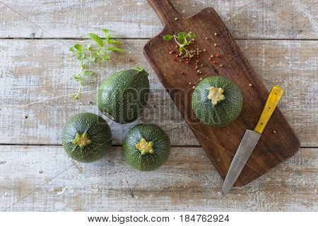 Round zucchini on a wooden table and cutting board.