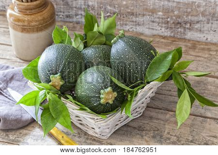 Round zucchini in a basket on a wooden table.