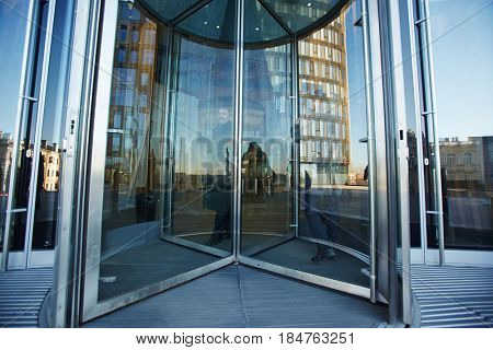Full-length portrait of senior businessman walking through revolving door of office building