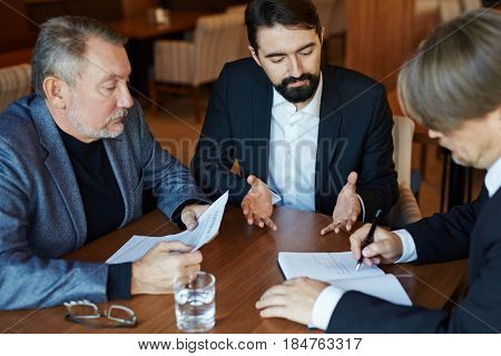 Productive business meeting in cozy restaurant: three businessmen in formalwear sitting around table and working hard to end joint project, waist-up portrait