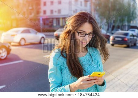 Beautiful young woman in glasses with a smartphone rewriting on the way to work on the background of cars