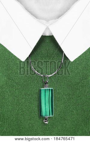 Malachite pendant over green pullover with white collar closeup