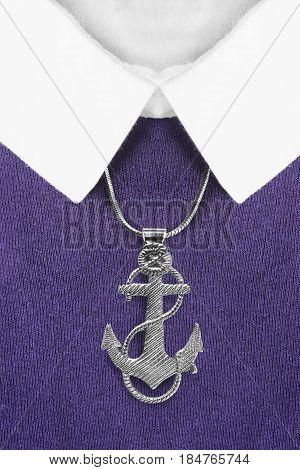 Silver anchor pendant over purple pullover with white collar closeup