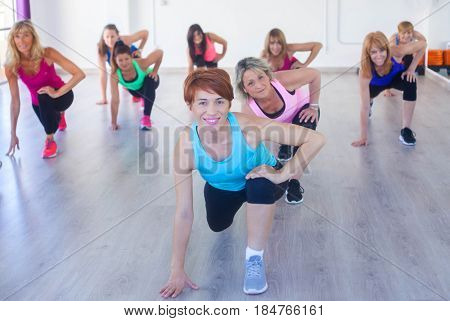 fit healthy women at gym class stretching,