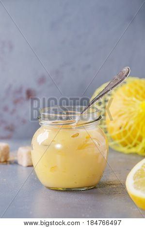 Jar of homemade lemon curd with spoon, whole and sliced lemons, sugar and zest over gray blue stone texture background.