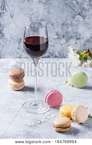 Glass of port wine with variety of colorful french sweet dessert macaron macaroons with different fillings served with spring flowers over gray texture background. Celebration concept