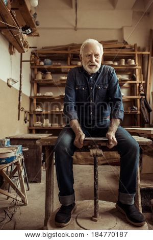 Front View Of Senior Man Sitting On Table And Working On Pottery Wheel