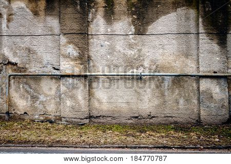 Old concrete wall with gas pipe and columns. Architecture detail background