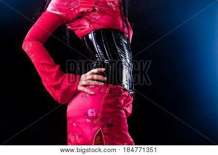 red geisha wearing black corset on dark background
