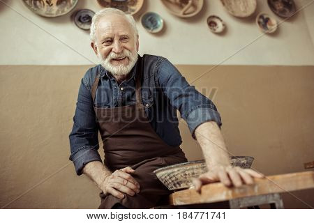 Senior Potter In Apron Sitting On Table Against Wall With Hanging Pottery Goods